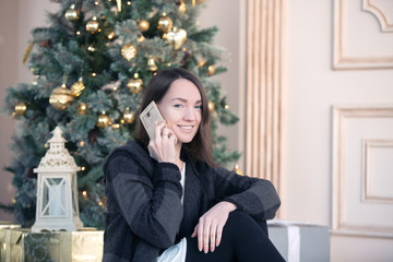 young girl congratulates by phone of the friends and relatives on Christmas and new year near christmas tree
