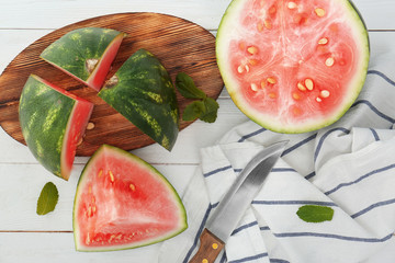Watermelon slices with knife on table