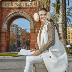 happy modern woman in Barcelona, Spain with map looking aside