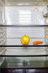 A yellow apple and a carrot on a shelf in a refrigerator