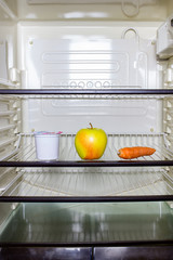 A yellow apple, a carrot eun yogurt container on a shelf in a refrigerator