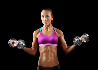 Sporty young woman with dumbbells on black background