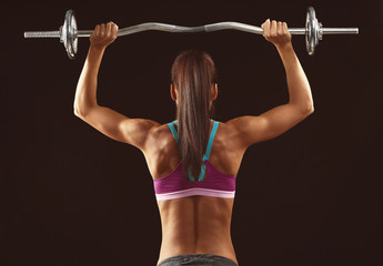 Sporty young woman with barbell  on black background