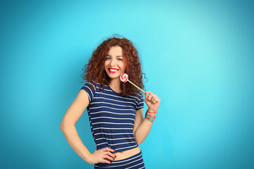 Portrait of expressive young model in striped suit with lollipop on blue background