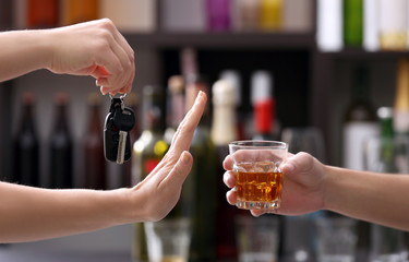 Woman with car key refusing glass of alcoholic beverage, on blurred background. Don't drink and drive concept