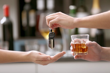 Drunk man giving car key to woman, on blurred background. Don't drink and drive concept