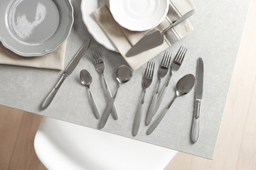 Cutlery set with plates on gray table,top view