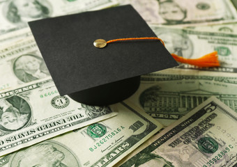Close up view of graduation hat on dollar banknotes. Tuition fees concept