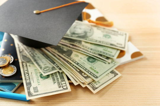 School supplies, graduation hat, dollar banknotes and coins on wooden table. Pocket money concept