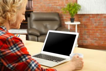 Senior woman making video call using laptop at home, closeup