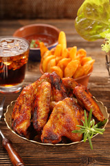 Chicken hot wings with baked potatoes and barbecue sauce