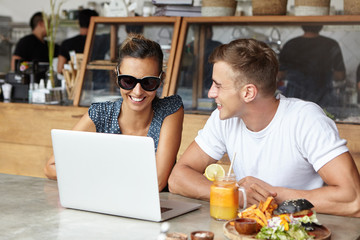 Modern technology and communication concept. Happy couple watching video or browsing pictures on internet using free wi-fi on generic laptop together while having lunch at cafe. Selective focus