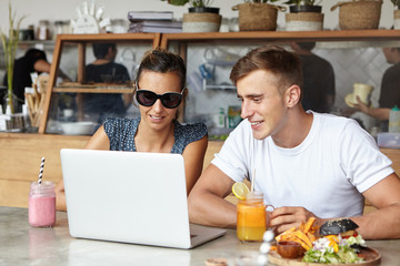 Two students talking, enjoying free wireless internet connection, using laptop computer, sitting at table with open notebook, fresh drinks and food during lunch break, looking at screen with interest