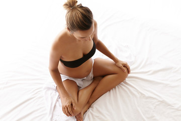Young future mother wearing black bra and white shorts sitting in lotus pose on her bed, resting hands on her knees and meditating alone in bedroom. Pregnant woman with hair knot relaxing indoors