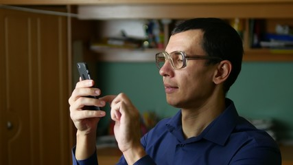 man glasses spectacled typing message on the phone smartphone social media