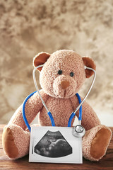 Teddy bear with ultrasound scan of baby and stethoscope on wooden table