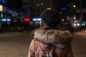 Lonely girl walking through night city street