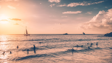 Tropical sunset beach with sailboat.