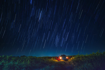 night scene of star tail and blue sky over car parking in agricu