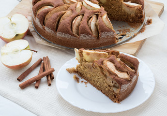 Vegetarian apple cake on a table with apple cut and cinnamon sticks