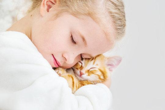 cute little girl holding a kitten on a ginger hand