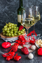 Bottle of white wine, two glasses and grapes bunch