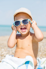 Happy Toddler baby sea trying on sunglasses