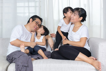 Happy Asian Chinese family kissing on the couch at home
