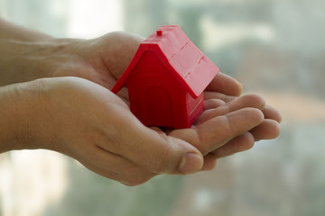Small red house in the man's hands