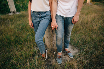 Couple in denim clothes. Couple in love in denim shoes and jeans, holding hands at outdoors.