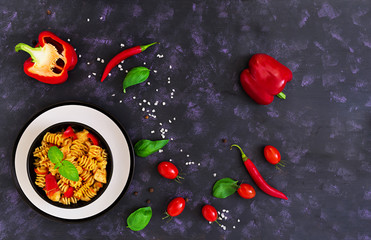 Radiatori pasta with chicken and peppers on dark background. Top view