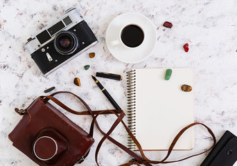 Flat lay, top view office table desk. Desk workspace with retro camera, diary, pen, glasses, case, cup of coffee on white background.