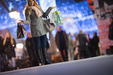 Happy pretty woman walking at night with christmas decorations.