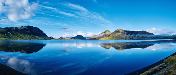 panoramic picture of Alftavatn Lake coast with mountain reflection at the sunrise, Iceland.