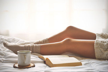 Soft photo of woman legs on the bed with old book and cup of coffee