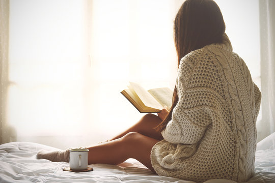 Young woman sitting in bed while reading a book