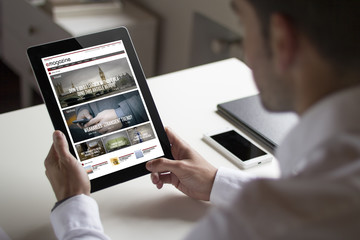 businessman reading online magazine with tablet pc