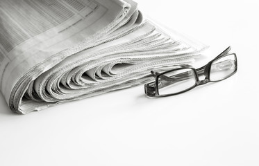 Newspapers with eyeglasses on white background