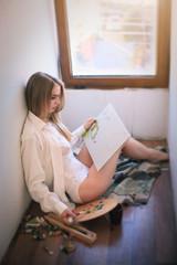 Beautiful woman in a shirt and underwear draws near the window.