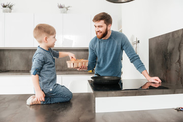 Bearded father cooking at kitchen with his little cute son
