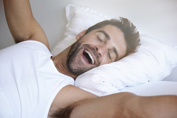 Yawning and stretching man waking in bed
