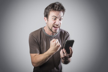 Stressed angry man is shouting at his cell phone, irritated with the service