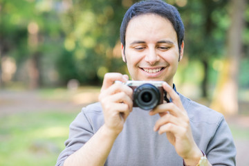 Smiling man using a mirrorless camera