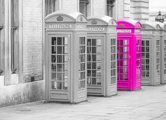 Five Red London Telephone boxes all in a row, in black and white with one booth in pink