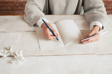 Unrecognizable woman writing in notebook mockup. Top view on table with author hands and some paper wads, free space for text. Writing, creation process, education concept