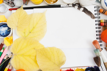 Yellow autumn leaves on blank sketchbook flat lay. Artist workplace, drawing fall motives. Art, workshop, painting, inspiration of autumn, craft, creativity concept