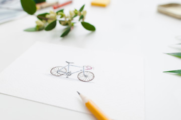 Colorful cute bicycle on greeting card, free space. Handmade picture of bike, drawn on white paper by pencil. Artist workplace, art, hobby, inspiration of sport concept
