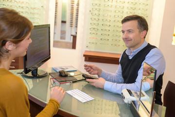 Optician and customer sat at desk