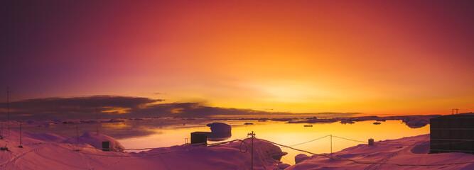 Kleurrijke zonsondergang in Antarctica. Oekraïense onderzoeksbasis - station Vernaskiy. Zonsonderganglicht weerspiegeld in het oceaanwater. Mooie winterse achtergrond.