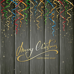 Christmas greeting and colorful tinsel on black wooden backgroun